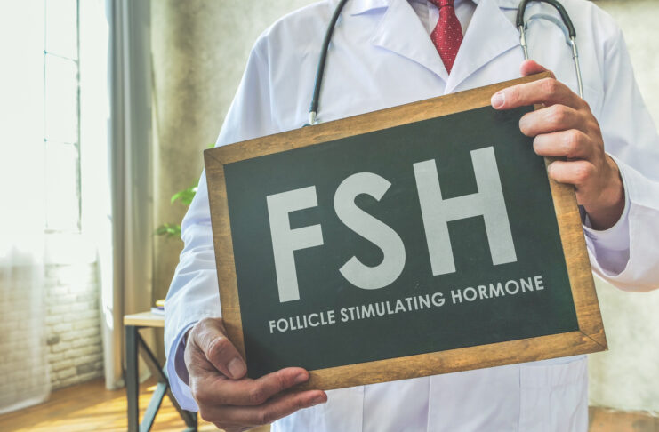 Dokter houdt bord FSH Follikel stimulerend hormoon op het bureau.