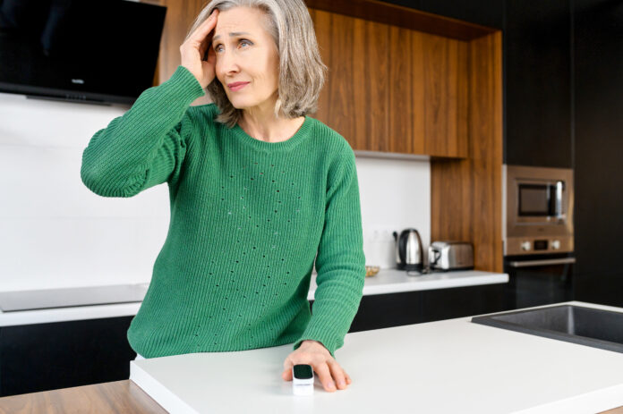 Elderly woman with wrinkles on the face, narrow lips, with a headache, sensitive to weather, checking blood pressure and pulse, leaning on the countertop in the kitchen, has an elegant grey hair