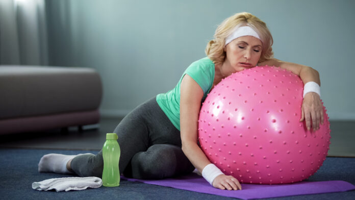 Exhausted mature female lying on fitness ball, relaxing after active workout