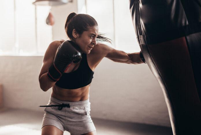 Female boxer hitting a huge punching bag at a boxing studio. Woman boxer training hard.