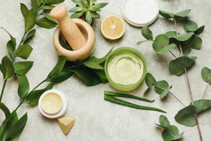 Composition à plat avec des produits cosmétiques sur fond gris. Boîtes de crème et de gel naturel, mortier pour mélanger les ingrédients. Produits de beauté naturels pour le soin de la peau.