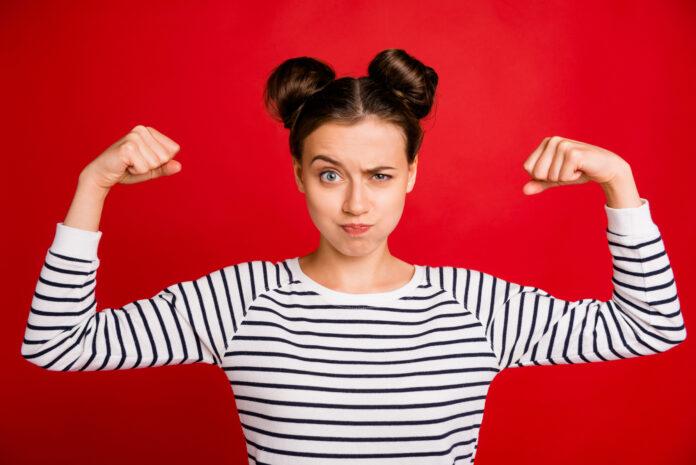 Lustige funky Teenager-Mädchen haben Bodybuilding Praxis zeigen Bizeps, Stärke aufblasen Wangen tragen lässigen Stil weiße Kleidung isoliert über helle Farbe Hintergrund