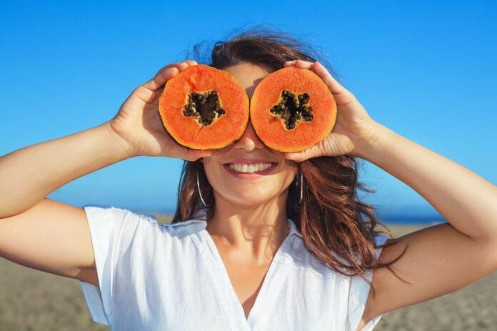 Lustiges Foto von positiven erwachsene Frau mit lächelndem Gesicht hält in den Händen reife Früchte - orange Papaya Scheiben. Gesundes Essen, kalorienarmes Frühstück am Meer Strand Gesunder Lebensstil im Sommer Familienurlaub