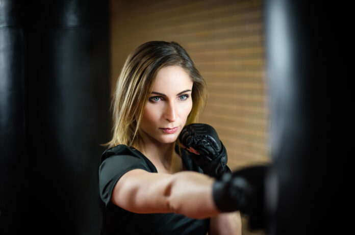 Girl and Boxing. Portrait of a girl in sportswear in Boxing gloves , mix mma open fingers gloves hits a black punching bag against the background of light brick wall. Fitness