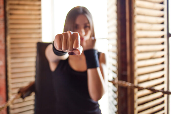 Girl fighter in the gym makes a blow to the camera, fist in focus