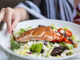 Grilled salmon salad with tomato, feta cheese, lettuce and so on and hand approaching.