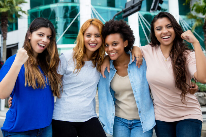 Group of four cheering young women outdoor in city