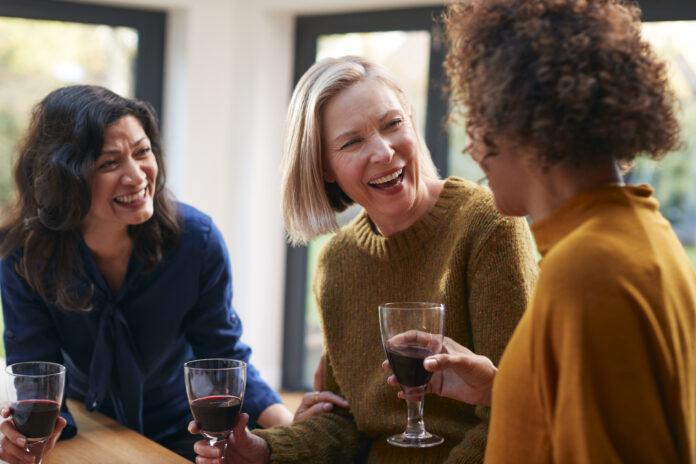 Groupe d'amies matures se réunissant à la maison pour parler et boire du vin ensemble.