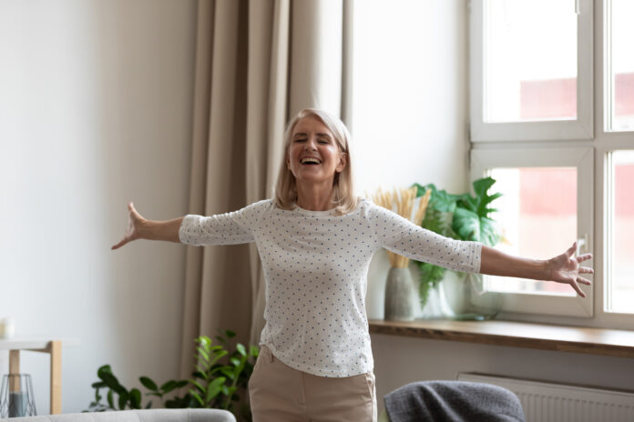 Happy mature female pensioner stand with arms open feel positive excited welcoming new good day, smiling senior middle-aged woman have fun satisfied with life, enjoy weekend leisure time