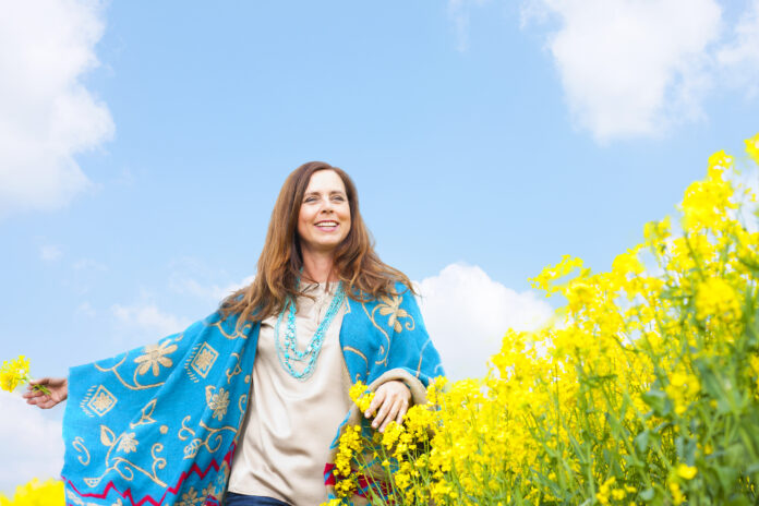 Happy middle scent woman in flower field with arms stretched
