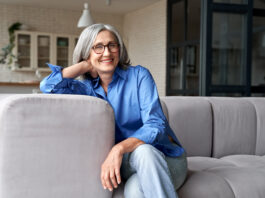 Happy relaxed mature old adult woman wearing glasses resting sitting on couch at home. Smiling mid age grey-haired elegant senior lady relaxing on comfortable sofa looking at camera. Portrait
