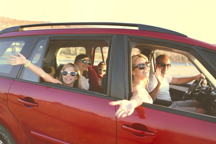 Happy smiling family with daughters in the car with sea background. Portrait of a smiling family with children at beach in the car. Holiday and travel concept
