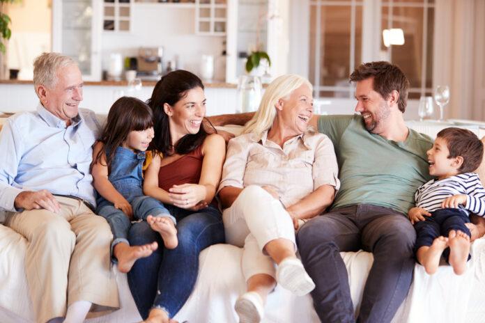 Glückliche weiße Familie in der dritten Generation, die zu Hause auf einem Sofa sitzt und sich gegenseitig anschaut, Vorderansicht