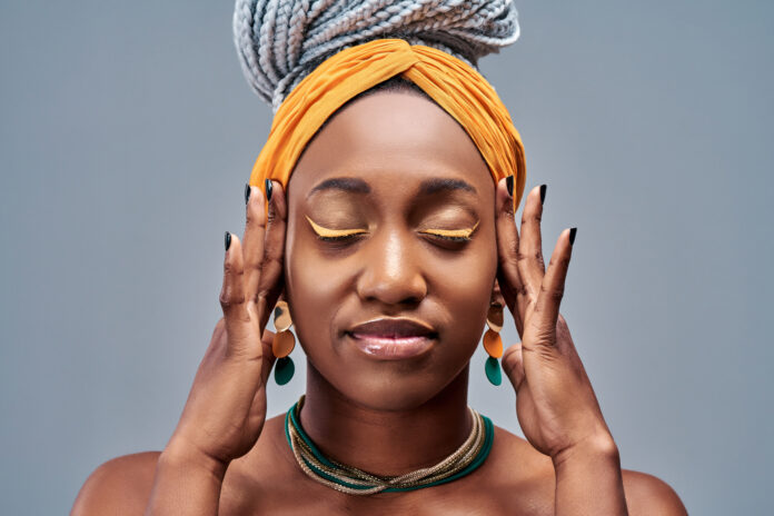 Head shot portrait afro american attractive calm woman isolated on grey background, closed eyes enjoying and dreaming about future feels satisfied and tranquil conceptual image.