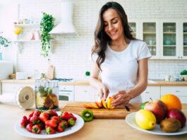 Gesunde Ernährung Lebensstil Konzept Porträt der schönen jungen Frau bereitet Getränk mit Bananen, Erdbeeren und Kiwi zu Hause in der Küche.