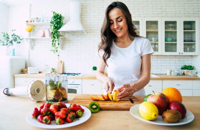 Portrait d'une belle jeune femme préparant une boisson avec des bananes, des fraises et des kiwis à la maison, dans la cuisine, dans le cadre d'un mode de vie sain.