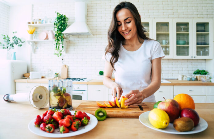 Healthy eating lifestyle concept portrait of beautiful young woman preparing drink with bananas, strawberry and kiwi at home in kitchen.
