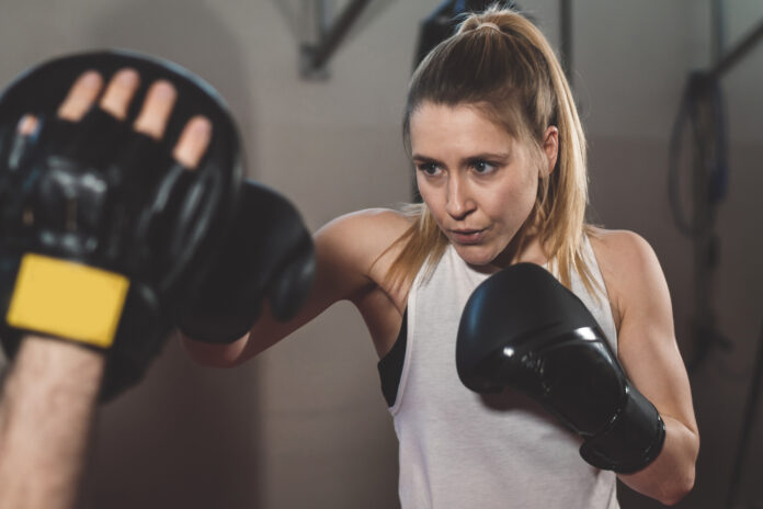 Healthy young female boxer wearing boxing gloves. Muscular built woman getting ready for boxing exercise at fitness studio. With copy space. I like to be safe on the streets, know how to defende myself. This is part of my healthy lifestyle routine.