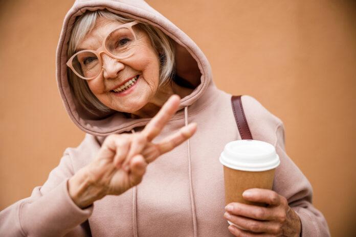 Fröhlich im Alter von Frau in Kapuze und Brille demonstriert Frieden Geste beim Trinken von Kaffee