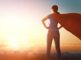 Vrolijke mooie jonge vrouw in superheldenkostuum poseert op zonsondergang achtergrond.