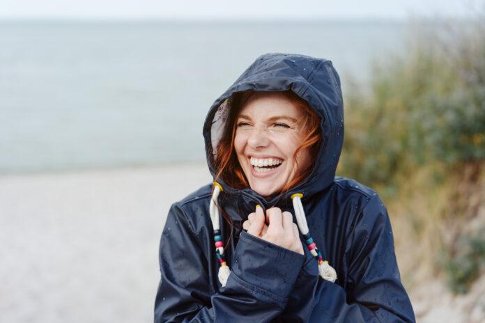 Lachende glückliche junge Frau, die das kalte Herbstwetter umarmt und sich mit einem strahlenden, lebhaften Lächeln in ihren warmen Anorak kuschelt, während sie am Strand entlang spaziert