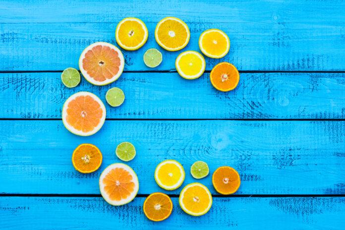 Litera C wykonana z owoców cytrusowych na rustykalnym niebieskim tle. Flat lay.