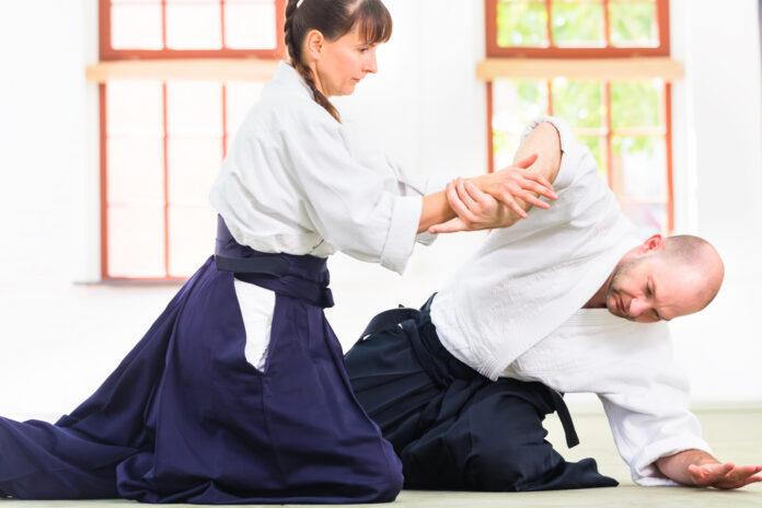 Homme et femme se battant lors d'un entraînement d'Aikido dans une école d'arts martiaux
