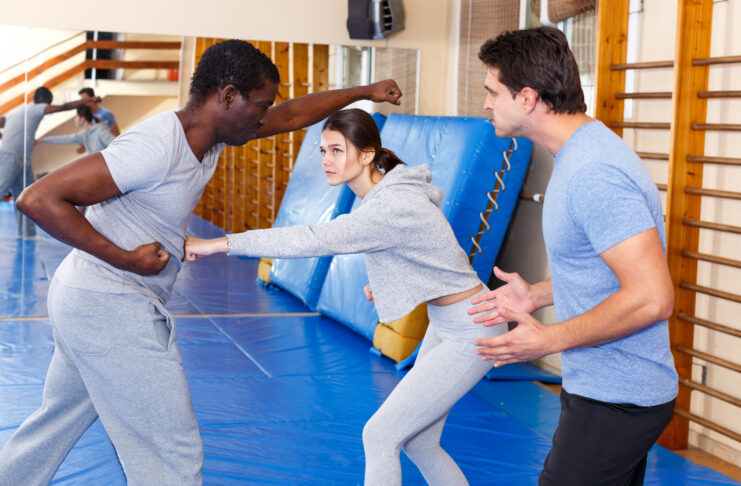 Man and woman in sportswear exercising self-protection techniques in pair at gym