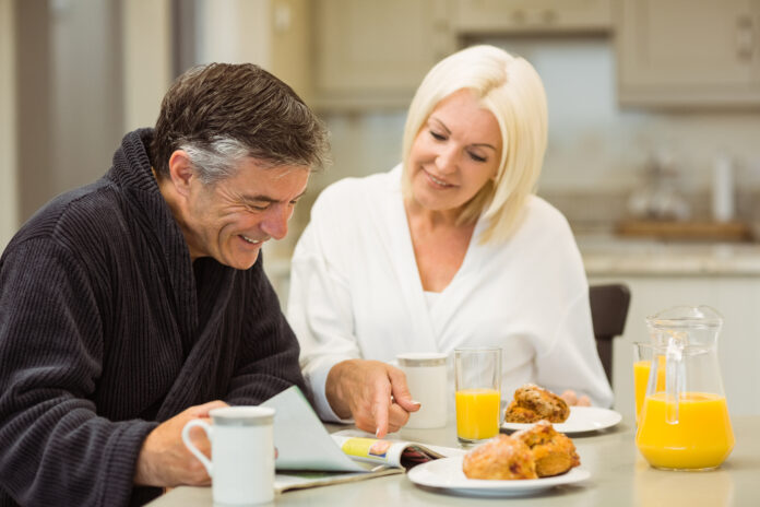 Mature couple having breakfast together at home in the kitchen