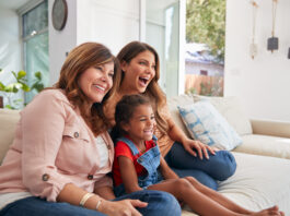 Vrouwelijke Hispanic familie van meerdere generaties op sofa thuis die samen TV kijkt