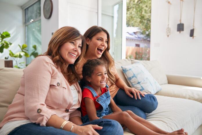 Multi-Generation Female Hispanic Familie auf Sofa zu Hause fernsehen zusammen