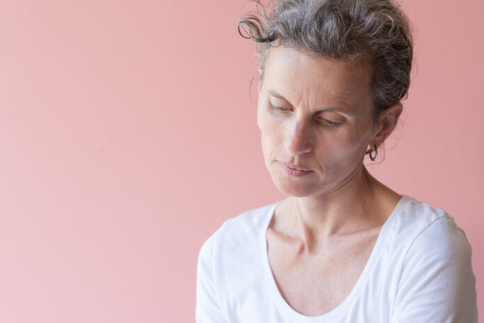 Natural looking middle aged woman with grey hair looking pensive against pink background (selective focus)