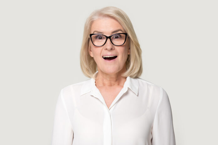 Old woman in glasses sincere surprised looking at camera. Beautiful mature female feeling astonished, wondered, amazed when meeting someone, seeing something interesting, unexpected. People emotions