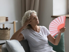 Overheated senior woman relax sit on sofa waving orange peach colour fan cool herself, feels unwell due unbearable hot weather, discomfort and hormonal changes, flat without air conditioner concept