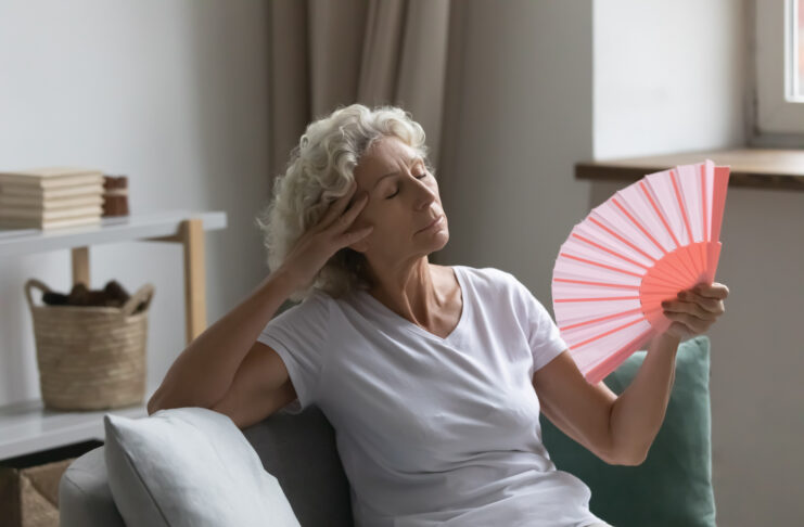De oververhitte oudere vrouw ontspant zit op bank wuivende oranje perzikkleurige ventilator koelt zich, voelt zich onwel wegens ondraaglijk heet weer, ongemak en hormonale veranderingen, flat zonder airconditioningsconcept