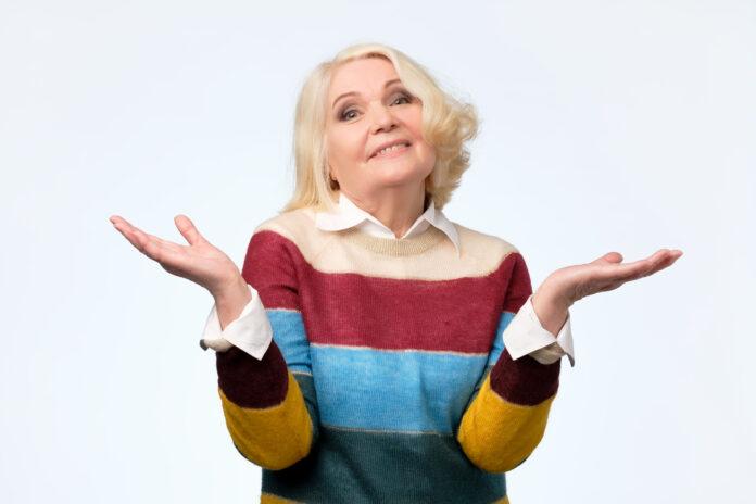Porträt einer netten älteren Frau mit einer zweifelnden Geste. Wer weiß oder ich weiß nicht, was zu wählen.