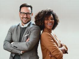 Retrato de una alegre pareja de negocios multiétnica con traje y mirando a la cámara