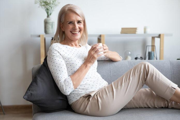 Portrait d'une femme d'âge moyen souriante, retraitée, assise et détendue sur un canapé confortable à la maison, dégustant une boisson chaude. Une femme d'âge mûr heureuse, grand-mère, se repose sur un canapé confortable et boit du café ou du thé, regarde l'appareil photo en posant.