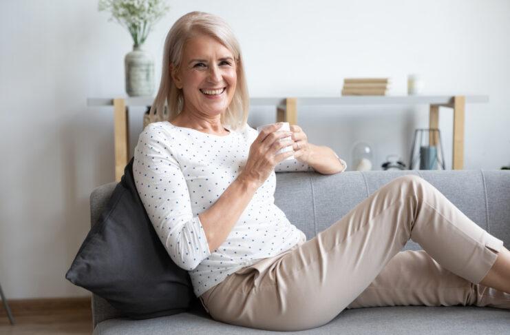 Retrato de sonriente jubilada de mediana edad sentada relajada en un acogedor sofá en casa disfrutando de una bebida caliente, mujer madura feliz descansando en un cómodo sofá bebiendo café o té, mirando a la cámara posando