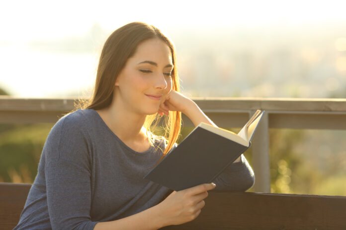 Relaxed woman reading a hard cover book at sunset sitting on a park bench