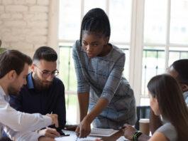 Sentados en el escritorio grupo empresarial multinacional y jefa africana jefe de equipo trabajando en proyecto analizando papel oficial de contrato cogitando sobre el problema juntos haciendo trabajo común en la sala de conferencias