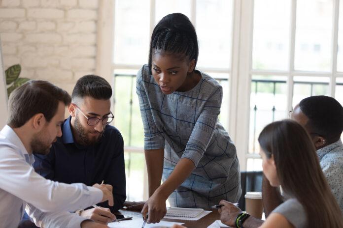 Sitzen am Schreibtisch multinationalen Business-Gruppe und afrikanischen weiblichen Chef Teamleiter arbeiten an Projekt analysieren Vertrag offiziellen Papier cogitating auf Problem zusammen tun gemeinsame Arbeit im Konferenzraum