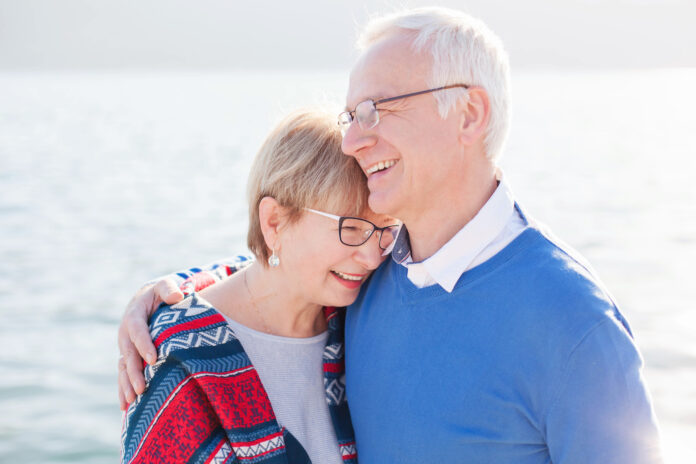 Senior couple is laughing, smiling at sea beach outdoor. Happy man and woman are hugging, embracing, enjoying retirement. Concept of wellbeing, happiness, male and female health, lifestyle moments.