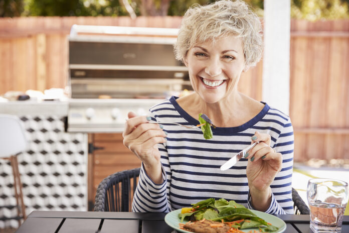 Senior white woman eating lunch at a table in her garden