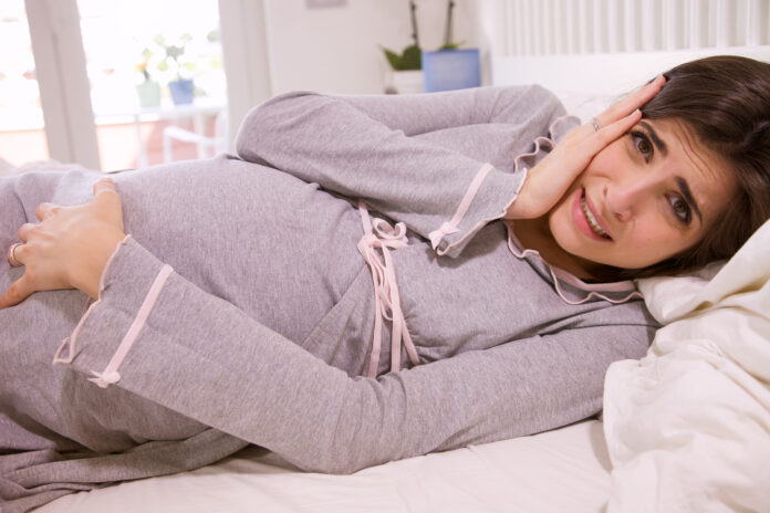 sick ill pregnant woman in bed