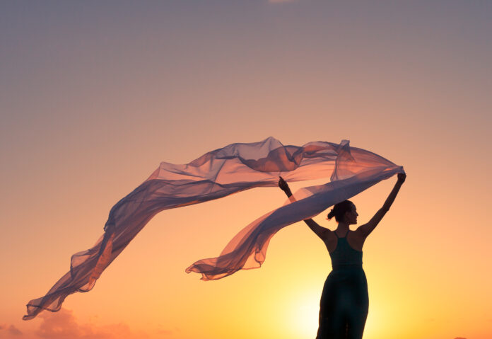 Silhouette of beautiful happy woman holding silk cloth blowing in the wind.