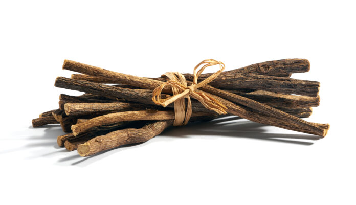 Single bundle of cut and dry licorice root tied with string over white background
