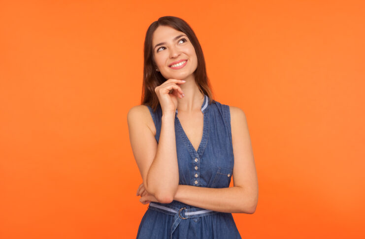 Smiling happy brunette woman in denim dress looking up with dreamy peaceful expression and imagining, thinking of pleasant memories, making wish. indoor studio shot isolated on orange background