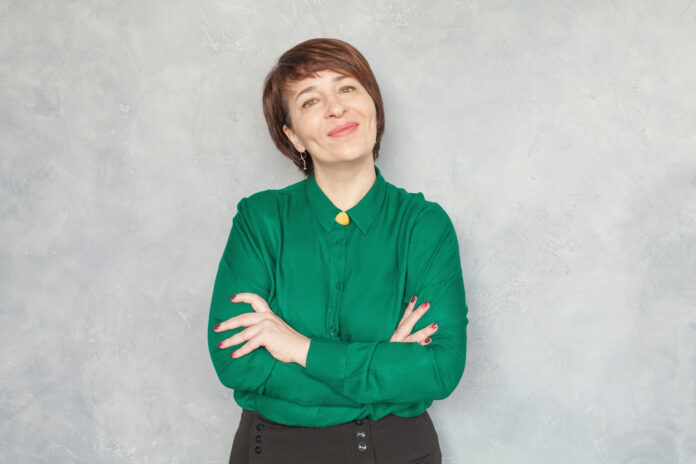 Smiling mature woman wearing green shirt on gray background, portrait