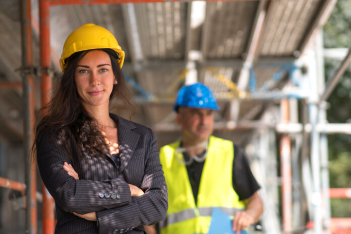 Smiling young woman construction manager or engineer posing looking at the camera with crossed arms. On background, out of focused construction worker